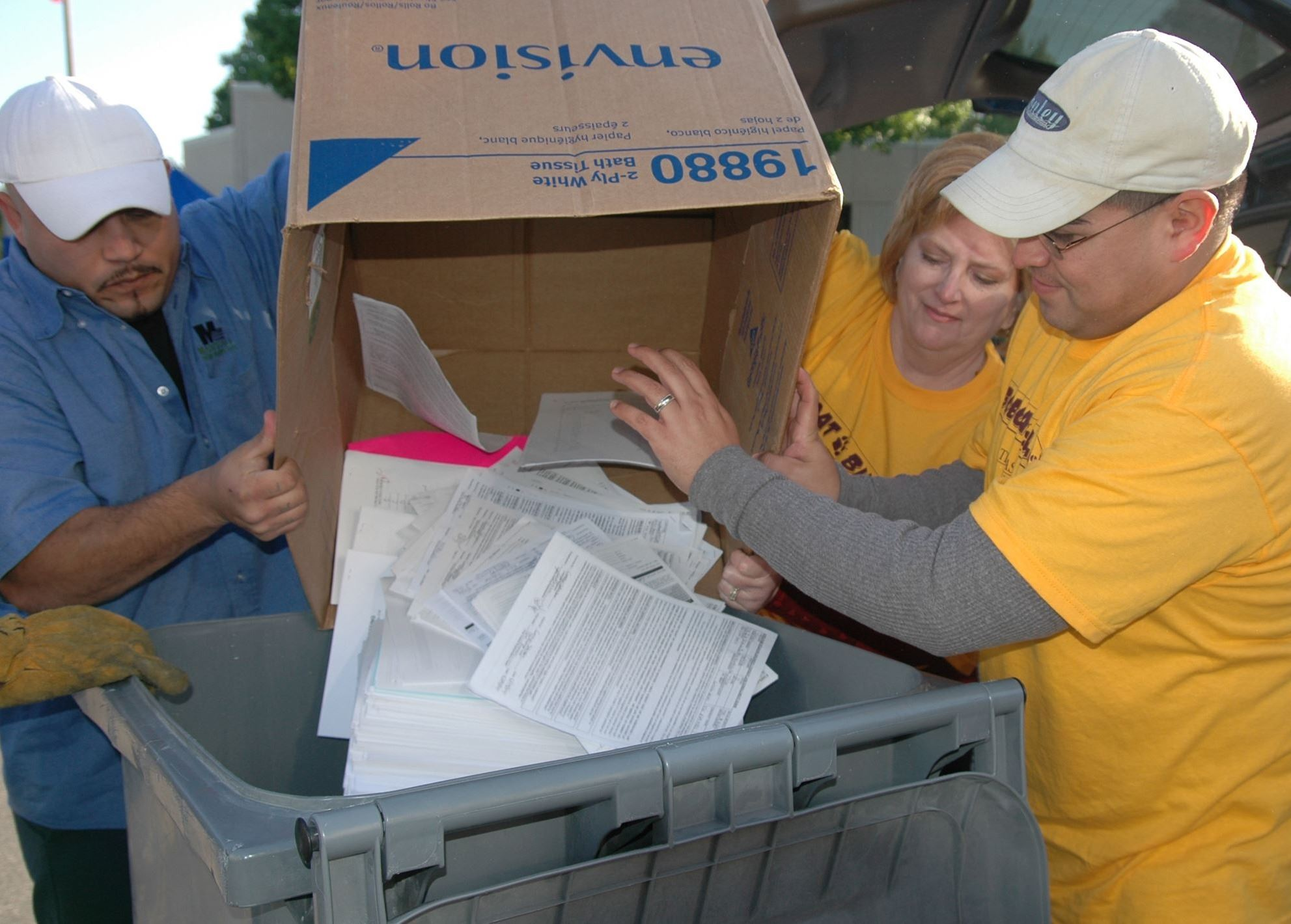 Photo of three people dumping paper from a box into a larger trash receptacle