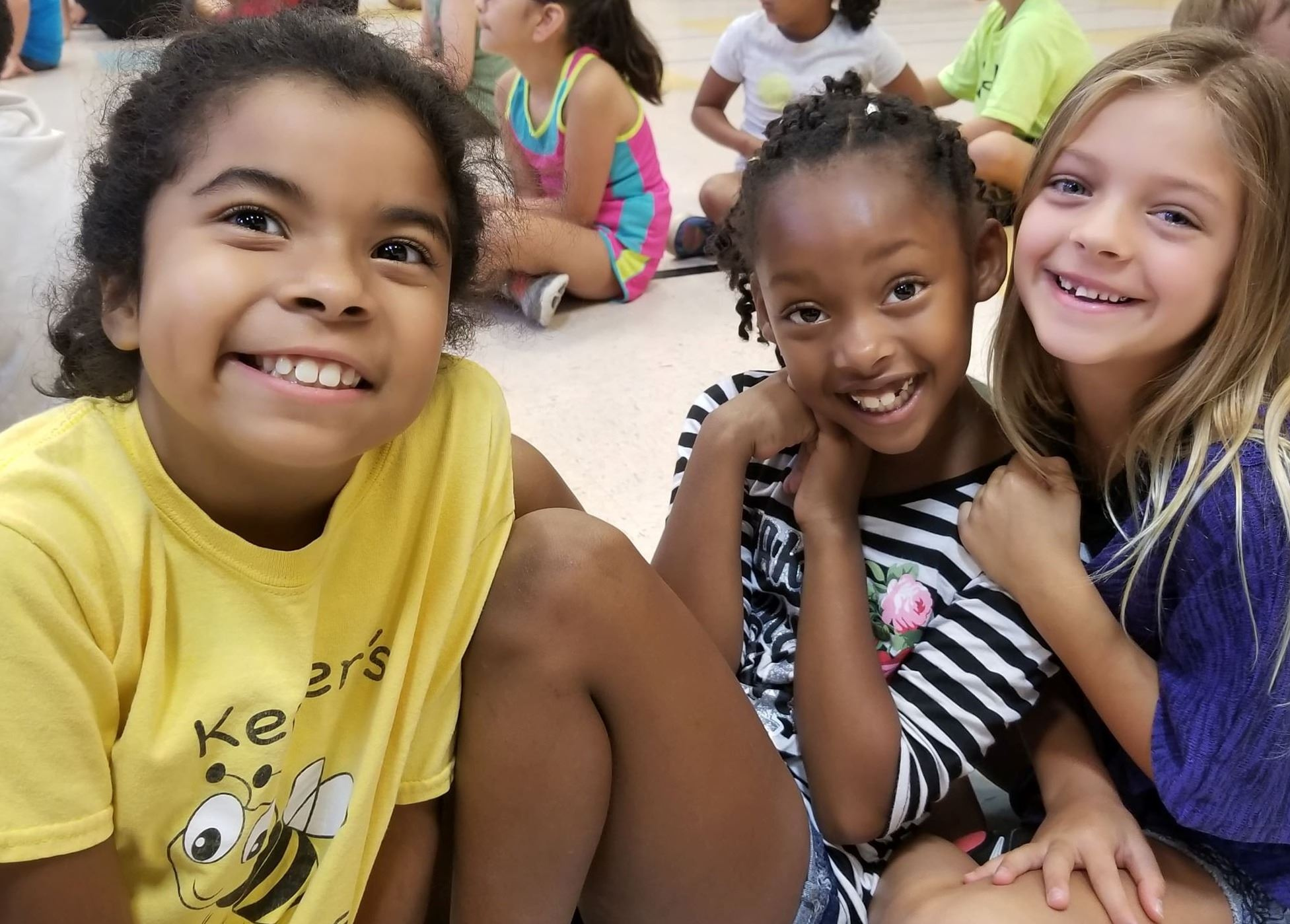 Photo of three smiling children at COSM Summer Camp