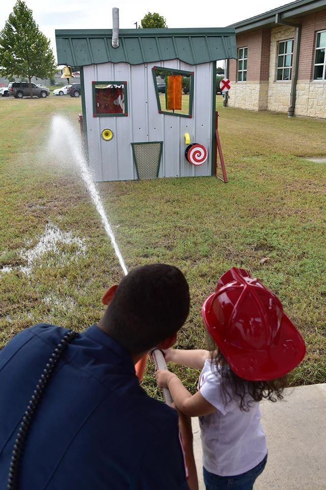 Kid Spraying Water on a Fake House