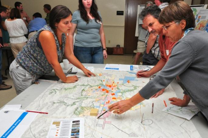 People Working on a Map at the Growth Scenario