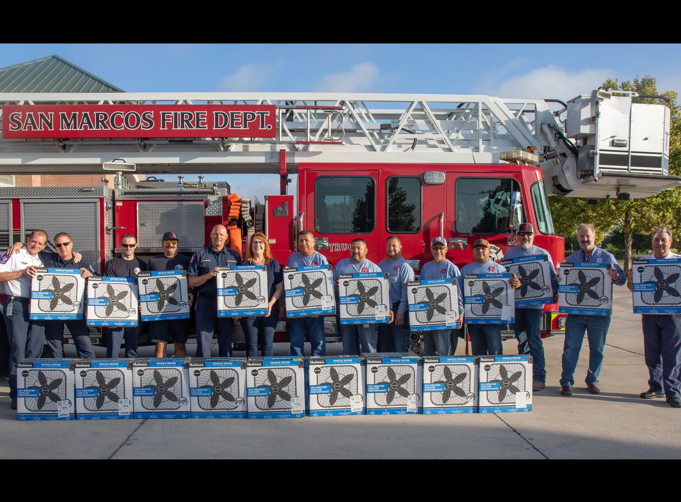 Photo of San Marcos Fire Department and Electric Utility employees holding donated fans in front of