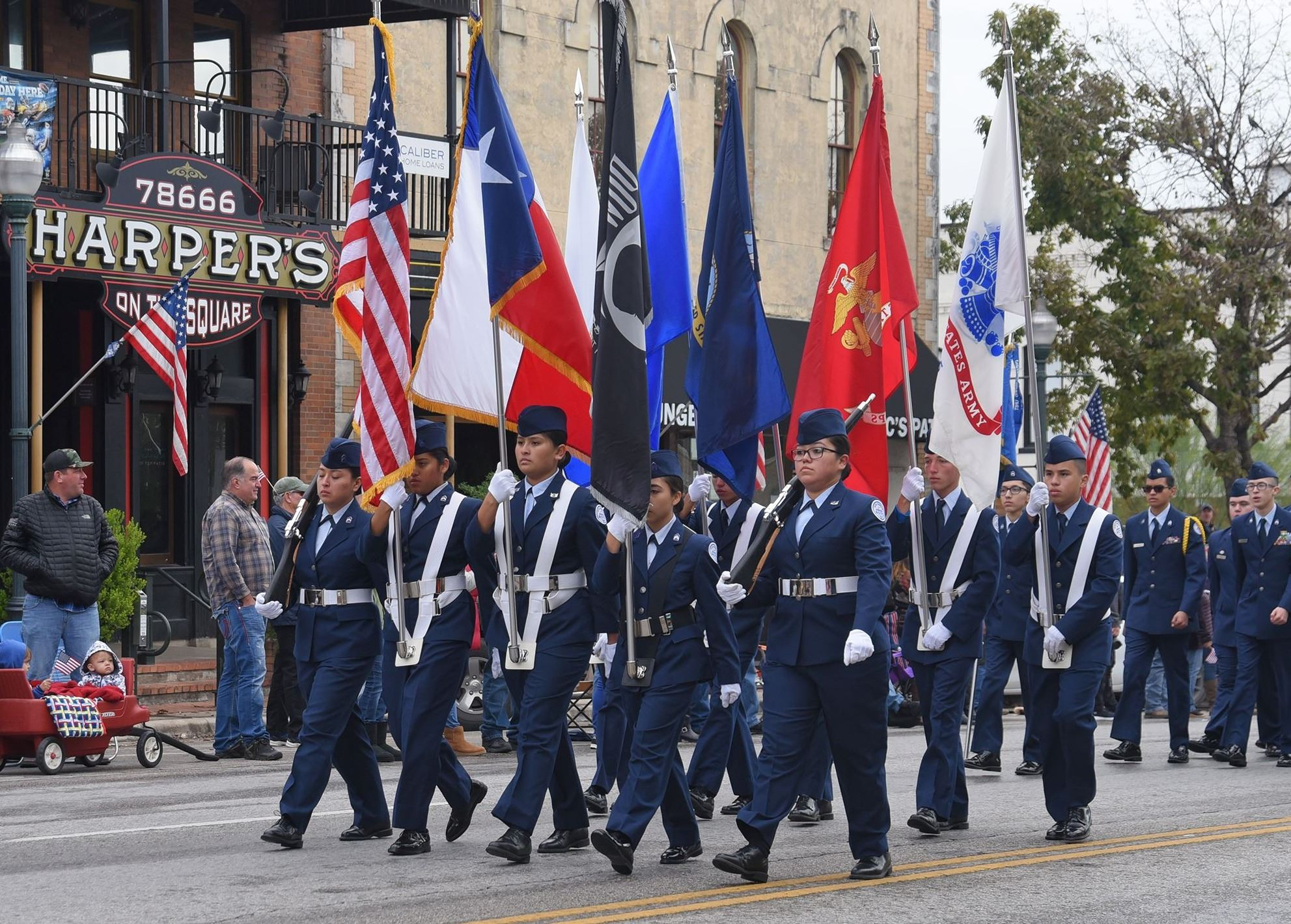 Photo of JROTC members carrying flags through downtown in 2018 Veterans Day Parade.