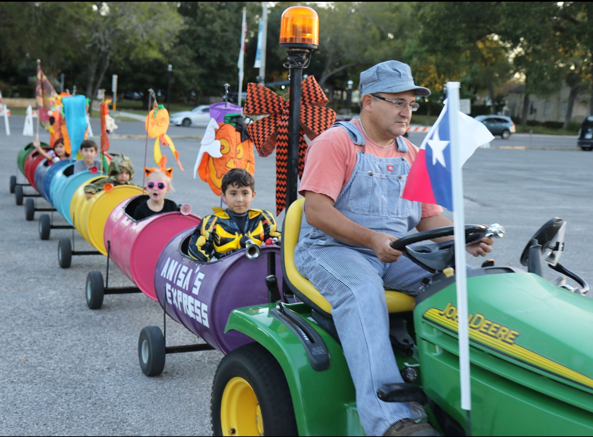 Children in costumes riding on a barrel train pulled by a tractor at the 2016 Fall Harvest Carnival.