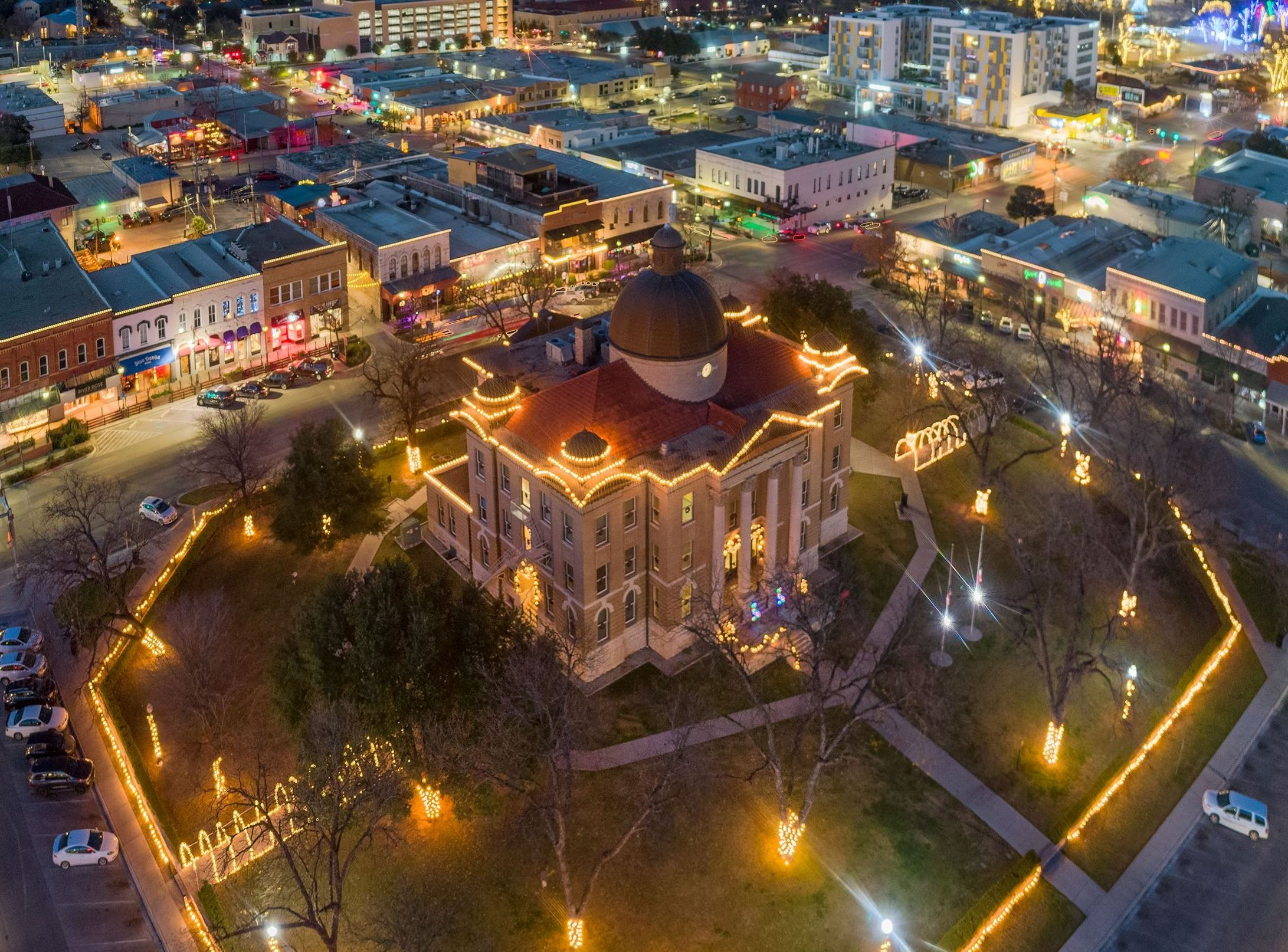 Aerial photo taken of Historic Hays County Courthouse with holiday lighting installed