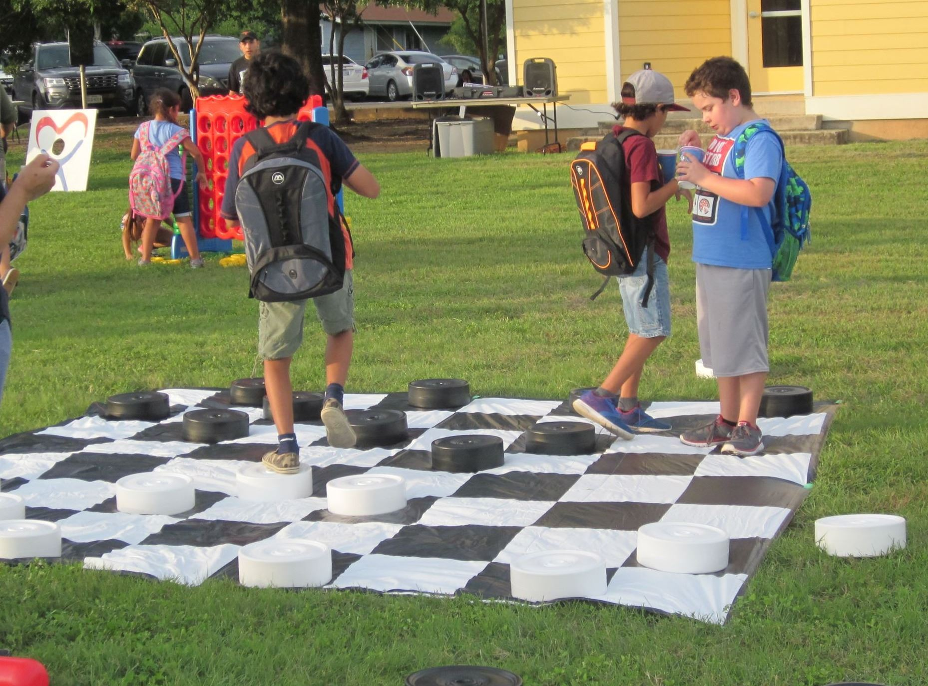 Photo of children playing on large chess board outside in a park