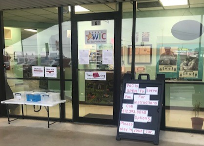 Photo of WIC Storefront with forms and dropoff area outside of door