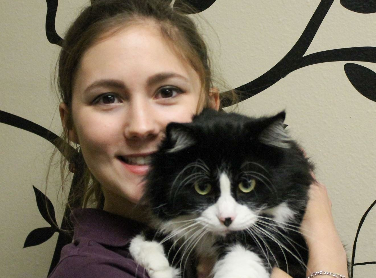 Nichole Nocki holding a long haired black and white cat